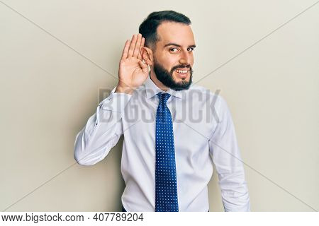 Young man with beard wearing business tie smiling with hand over ear listening an hearing to rumor or gossip. deafness concept.