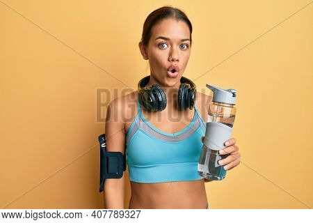 Beautiful hispanic woman wearing sportswear drinking bottle of water scared and amazed with open mouth for surprise, disbelief face