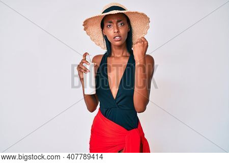Young african american woman wearing swimsuit and holding sunscreen lotion annoyed and frustrated shouting with anger, yelling crazy with anger and hand raised