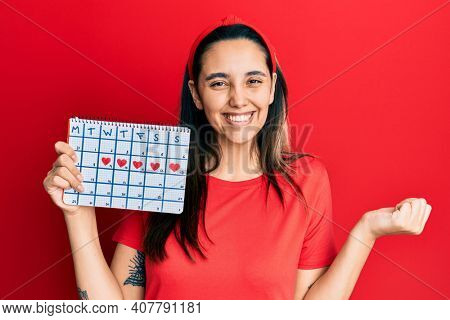 Young hispanic woman holding heart calendar screaming proud, celebrating victory and success very excited with raised arm