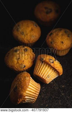 Vanilla muffins. Sweet cupcakes on black table.