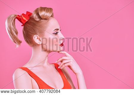Pin-up beauty concept. Profile portrait of a stunning blonde woman with make-up and hair in pin-up style on a pink background. Valentine's Day. Copy space.