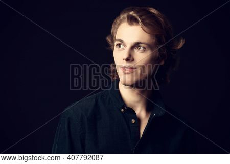 Portrait of a handsome young man with wavy blond hair looking away and smiling. Black background with copy space. Men's beauty.