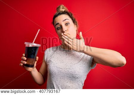 Beautiful blonde woman drinking cola fizzy beverage to refreshment over red background cover mouth with hand shocked with shame for mistake, expression of fear, scared in silence, secret concept