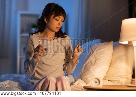 people, health and bedtime concept - stressed asian american woman having headache and taking medicine or sleeping pill with water in bed at night