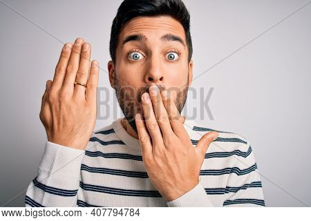 Handsome man with beard showing alliance ring marriage on finger over white background cover mouth with hand shocked with shame for mistake, expression of fear, scared in silence, secret concept