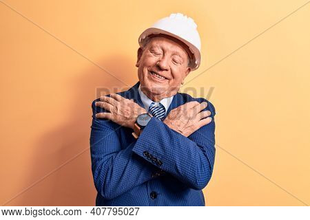Senior grey-haired architect man wearing suit and security hardhat over yellow background hugging oneself happy and positive, smiling confident. Self love and self care