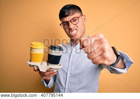 Young scholarship holder business man holding take away coffee over isolated yellow background annoyed and frustrated shouting with anger, crazy and yelling with raised hand, anger concept