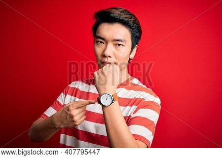 Young handsome chinese man wearing casual striped t-shirt standing over red background In hurry pointing to watch time, impatience, looking at the camera with relaxed expression