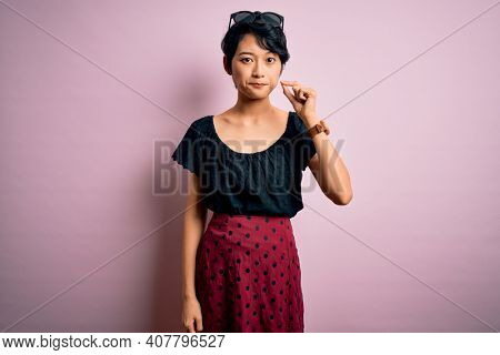 Young beautiful asian girl wearing casual dress standing over isolated pink background mouth and lips shut as zip with fingers. Secret and silent, taboo talking