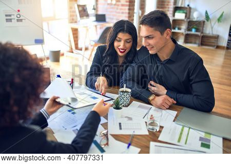 Young beautiful couple applying for mortgage. Sitting smiling happy meeting with real state agent considering mortgage loan at bank