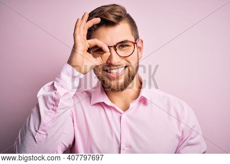 Young handsome blond man with beard and blue eyes wearing pink shirt and glasses doing ok gesture with hand smiling, eye looking through fingers with happy face.