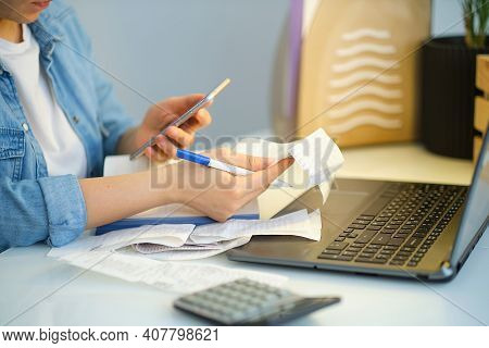 Woman Using A Pen Writing On Bank Account Book While Holding The Bills To Calculate In Living Room A
