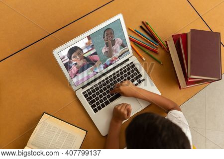 Overhead view of male student having a video conference with multiple students on laptop at school. distance learning online education concept
