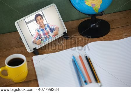 Mixed race schoolboy learning on tablet screen on desk during video call. Online education staying at home in self isolation during quarantine lockdown.