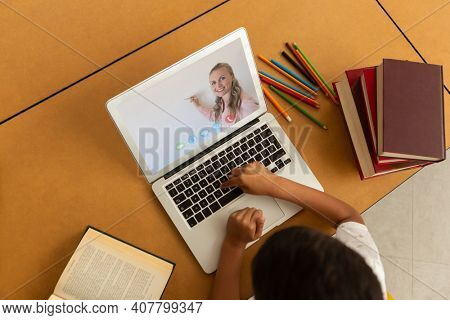 Overhead view of male student having a video call with female teacher on laptop at school. distance learning online education concept