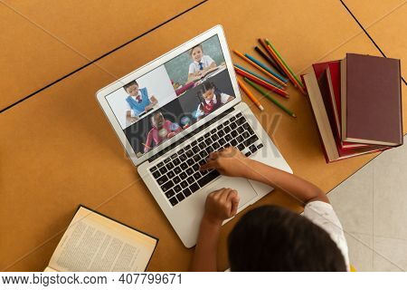 Overhead view of male student having a video conference with other students on laptop at home. distance learning online education concept