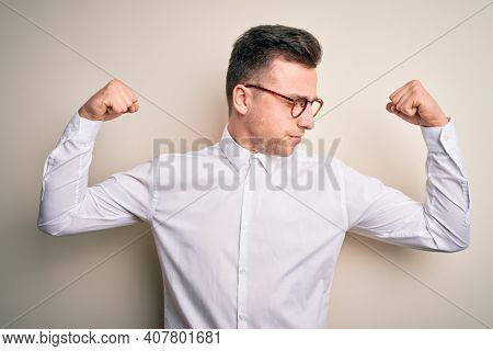 Young handsome business mas wearing glasses and elegant shirt over isolated background showing arms muscles smiling proud. Fitness concept.