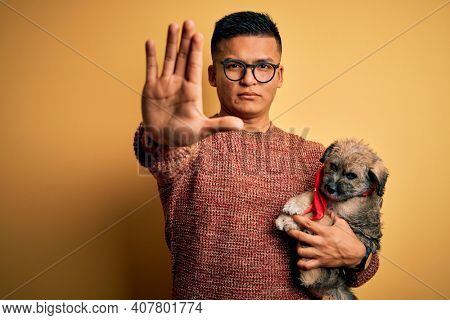 Young handsome latin man holding cute puppy pet over isolated yellow background with open hand doing stop sign with serious and confident expression, defense gesture