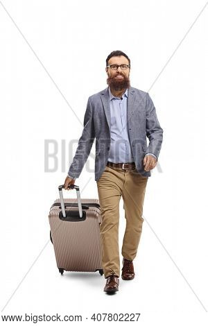 Full length portrait of a bearded man pulling a suitcase and walking towards the camera isolated on white background