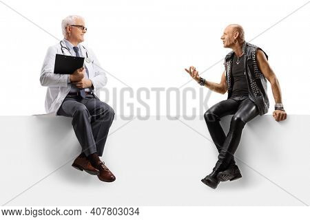 Mature doctor and a bald punk rocker seated on a blank panel talking isolated on white background