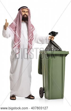 Full length portrait of a saudi arab man throwing a plastic bag in a waste bin and showing thumbs up isolated on white background