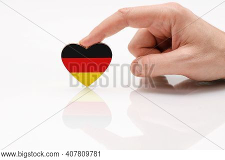 Love And Respect Germany. A Man's Hand Holds A Heart In The Shape Of The Germany Flag On A White Gla