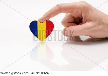 Love And Respect Romania. A Man's Hand Holds A Heart In The Shape Of The Romania Flag On A White Gla