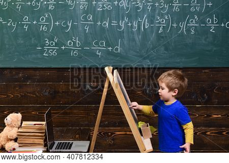 Little Child Writing On Chalkboard. Kid In Front Of Board With Math Equation. Smart Pupil Studying M