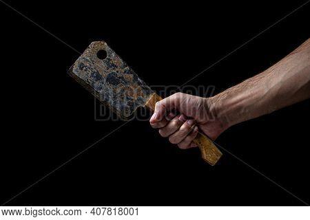 Old Kitchen Hatchet On A Black Background. A Man's Hand Holds A Kitchen Hatchet. Kitchen Tool