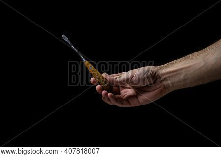 Antique Screwdriver On A Black Background. Male Hand Holds A Screwdriver. Steel Screwdriver With Woo