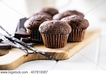 Chocolate muffins. Sweet dark cupcakes with chocolate and vanilla pods on cutting board.