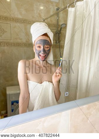 Young Woman Applies A Nourishing Gray Clay Mask To Her Face In The Bathroom, Looking In The Mirror,