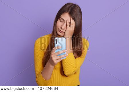 Face Palm From Stupid News, Upset Young Woman With Long Hair, Covering Face With Hand, Holding Smart
