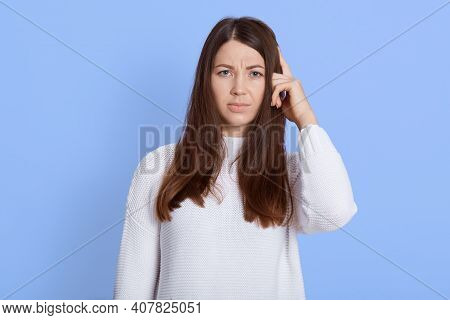 Portrait Of Forgetful Female Dark Haired Female Remembers Something, Keeps Finger On Temple, Remembe