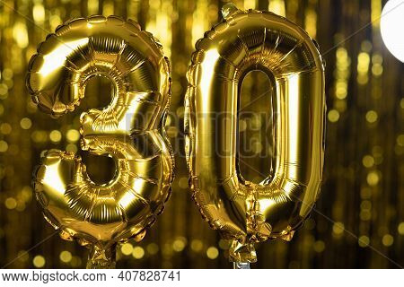The Golden Number 30 Thirty Is Made From An Inflatable Balloon On A Yellow Background. One Of The Co