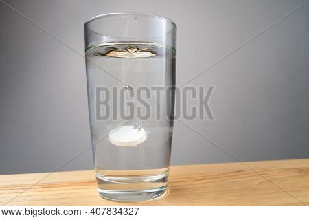 A Soluble Tablet Dropped In A Glass Of Water Over White Background.