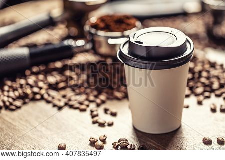 Paper Takeaway Cup With A Plastic Lid With A Coffee With Coffee Beans And Ground Coffee In The Backg