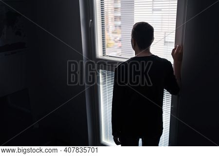 Lonely Man Looking Out The Window. Solitude, Isolation And Loneliness Concept. Sad Upset Person With