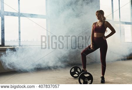 Full Body Slim Female Athlete In Sportswear Holding Hand On Waist And Stepping On Barbell While Stan