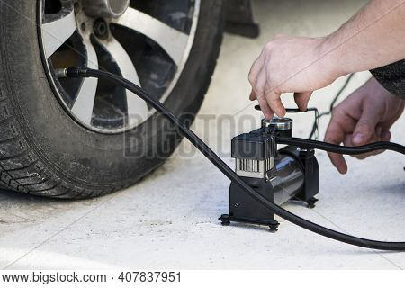 Car Compressor Wheel Pump. A Person Checks The Air Pressure And Fills The Tires Of His Car With Air.