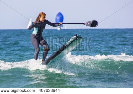 Young Girl With Wetsuit On Inflatable Surfboard Paddle Surf Falling Into The Water. Loss Of Balance