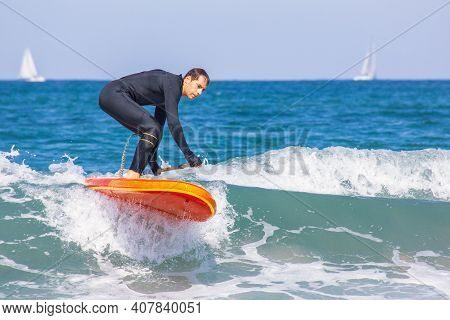 Man Sup Surfer Has Caught The Wave And Has Fun Paddle Surfing. Actve Man With Wetsuit In The Sea In