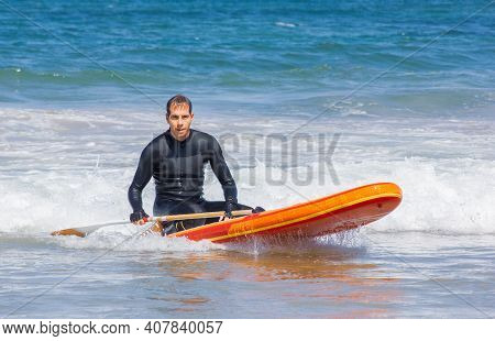 Inflatable Stand-up Paddle Board. Adult Man In Wetsuit Sitting On A Board And Looking At The Camera