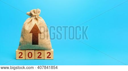 Money Bag And Up Arrow With Wooden Blocks 2022. Business Forecasting. Growth And Development Of Busi