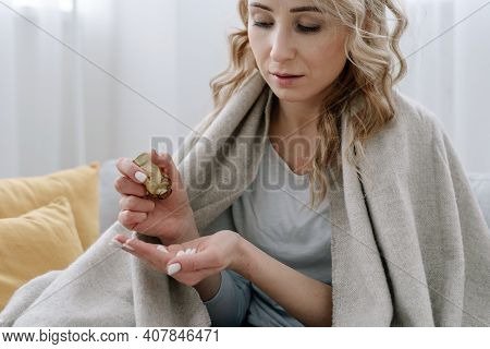 Vitamin, Multivitamin And Supplements Concept. Ill And Calm Woman Covered With Plaid, Sit On Sofa At