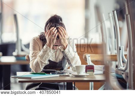 Female Busines Owner Holds Her Head In Hands In Desperation Over Paperwork And Tax Declaration In A