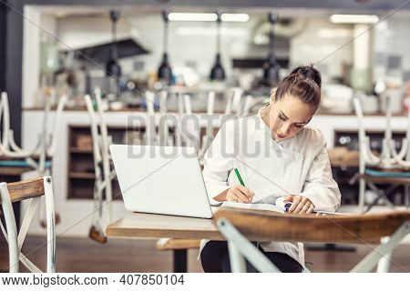 Female Restaurant Chef Sits At The Table After Hours Doing Her Bookkeeping In Front Of An Open Lapto
