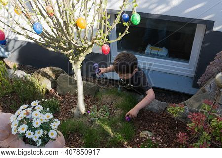 Heiligenhaus, Nrw, Germany - April 21, 2019: Little Boy Is Looking For Colorful Easter Eggs In The P