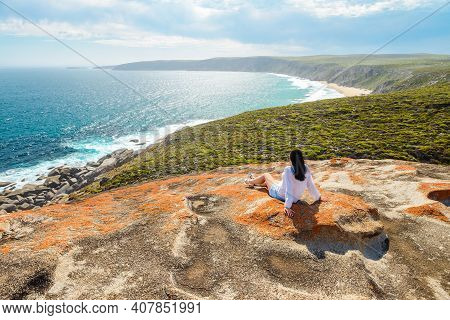 Woman Enjoying The Scenery While Sitting On The Edge Of The Cliff At Remarkable Rocks, Kangaroo Isla
